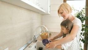 La madre enseña a la hija a lavar platos almacen de metraje de vídeo