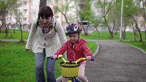 La madre enseña a la pequeña hija a montar una bicicleta