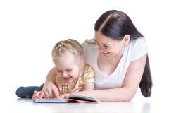 La madre enseña al libro de lectura al niño Imágenes de archivo libres de regalías
