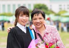 La madre está abrazando a su hija para su graduación del masters fotos de archivo