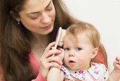 La madre está enseñando a la hija a cepillar el pelo. Foto de archivo libre de regalías