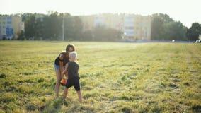 La madre está jugando la bola con el pequeño niño en hierba en Niza la puesta del sol metrajes