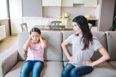 la madre está mirando a la hija Ella está trastornada La muchacha ha cerrado los oídos con las manos Ella el ` t del doesn quiere imágenes de archivo libres de regalías