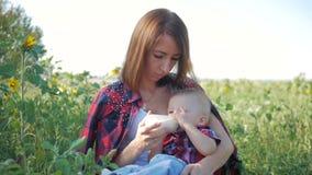 La madre felice alimenta il latte del biberon, all'aperto stock footage