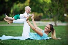 La madre felice allegra sta facendo l'allenamento su prato inglese con il piccolo figlio Mette in mostra il concetto, ora legale Fotografia Stock Libera da Diritti