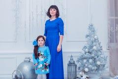 La madre felice con sua figlia in vestiti blu lunghi sta vicino all'albero di Natale Fotografie Stock