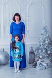La madre felice con sua figlia in vestiti blu lunghi sta vicino all'albero di Natale Immagine Stock