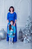 La madre felice con sua figlia in vestiti blu lunghi sta vicino all'albero di Natale Immagine Stock Libera da Diritti