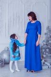 La madre felice con sua figlia in vestiti blu lunghi sta vicino all'albero di Natale Immagini Stock