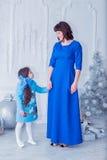 La madre felice con sua figlia in vestiti blu lunghi sta vicino all'albero di Natale Fotografia Stock Libera da Diritti