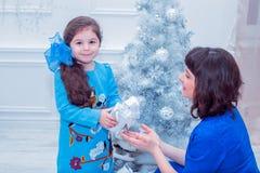 La madre felice con sua figlia in vestiti blu lunghi sta vicino all'albero di Natale Fotografia Stock