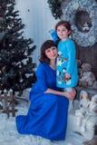 La madre felice con sua figlia in vestiti blu lunghi sta vicino all'albero di Natale Fotografie Stock Libere da Diritti