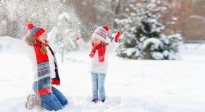 La madre felice ed il bambino della famiglia che giocano sull'inverno camminano Fotografie Stock