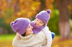 La madre felice ed il figlio che giocano in autunno parcheggiano Immagini Stock