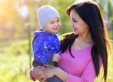 La madre felice ed il suo bambino godono della primavera in anticipo in parco Fotografia Stock Libera da Diritti