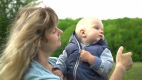 La madre felice ha un resto con il suo bambino sveglio nel movimento lento del parco stock footage