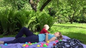 La madre felice mette sul plaid con la figlia del bambino sul plaid nel parco dell'estate 4K stock footage