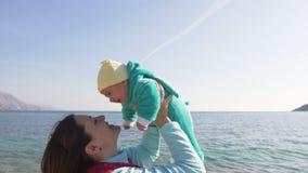 La madre felice tiene il suo poco bambino sulle mani sulla spiaggia un giorno di molla soleggiato stock footage