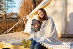 La madre feliz abraza a su niño con una manta mientras que se sienta cerca de la tienda de campaña imagen de archivo