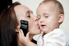 La madre feliz besa a la hija Foto de archivo