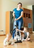 La madre feliz con dos niños limpia en casa Fotografía de archivo libre de regalías