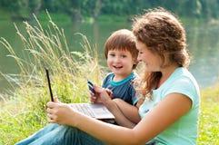 La madre feliz con el hijo está trabajando en su ordenador portátil en el río Imágenes de archivo libres de regalías