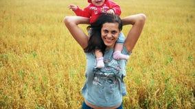 La madre feliz con el niño joven ríe en el campo del trigo metrajes