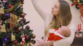 La madre feliz con la hija adorable en las manos adorna el árbol de navidad junta almacen de video
