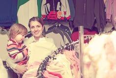 La madre feliz con la niña elige desgaste Imagen de archivo libre de regalías