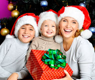 La madre feliz con los niños celebra el regalo del Año Nuevo Imagenes de archivo