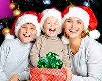 La madre feliz con los niños celebra el regalo del Año Nuevo Fotos de archivo libres de regalías