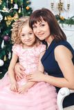 La madre feliz con su hija se sienta cerca de una chimenea blanca al lado de un árbol adornado con los juguetes Foto de archivo libre de regalías