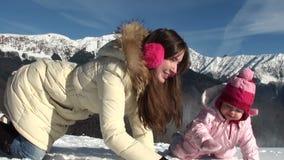 La madre feliz con su hija sonriente esculpe metrajes
