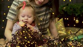 La madre feliz de la familia y la hija del bebé pequeña que juega en el invierno para los días de fiesta de la Navidad, chispea f metrajes