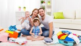 La madre feliz de la familia, el padre y dos niños embalaron las maletas FO Imagen de archivo