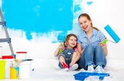 La madre feliz de la familia y la hija del niño que repara, pintan wal Imágenes de archivo libres de regalías