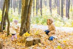 La madre feliz de la familia y la muchacha del niño que juega el tiro se va en parque del otoño al aire libre Fotos de archivo libres de regalías