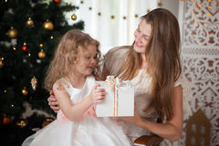 La madre feliz en la chaqueta blanca da el regalo a una hija en la Navidad Imagenes de archivo