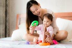 La madre feliz enseña a habilidades de 2 años de la coordinación de la hija usando los juguetes plásticos del aro imágenes de archivo libres de regalías