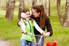 La madre feliz enseña a su hija a montar una bici La madre apoya positivamente a la hija que aprende montar una bicicleta Imagen de archivo libre de regalías