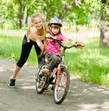 La madre feliz enseña a su hija a montar una bici Fotografía de archivo libre de regalías