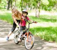 La madre feliz enseña a su hija a montar una bici Fotos de archivo
