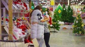 La madre feliz está poniendo el sombrero de Santa Claus en su hijo y lo está abrazando Gasto del tiempo en la alameda metrajes