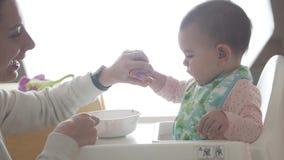 La madre feliz joven enseña a su bebé a comer sola de la cuchara, alimentos para niños almacen de metraje de vídeo