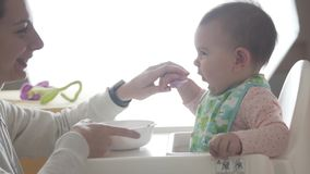 La madre feliz joven ense?a a su beb? a comer sola de la cuchara, alimentos para ni?os almacen de video