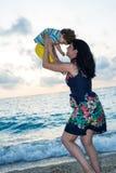 La madre feliz lanza para arriba al hijo en la playa Foto de archivo