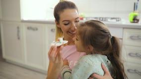La madre feliz toma el pelo a su hija con la galleta que juega en una cocina almacen de video