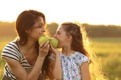 La madre feliz y la diversión que gozan de la muchacha del niño tienen una comida campestre y una consumición Imagen de archivo
