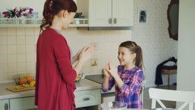 La madre feliz y la hija divertida linda que juegan al juego de las manos que aplaude y se divierten mientras que cocina en cocin almacen de video