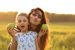 La madre feliz y la muchacha emocionada diversión del niño tienen una comida campestre y t de la consumición Imagen de archivo libre de regalías